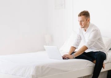 Man working with a laptop on his bed.