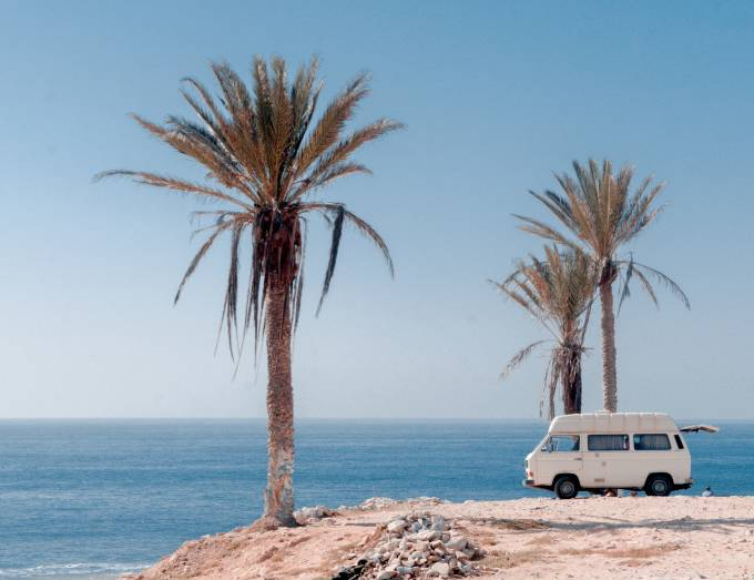 Van on the beach with palm trees.