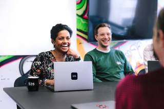 Two people sitting on a meeting room table in front of a computer smiling.