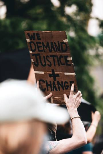 People marching holding justice and change sign.