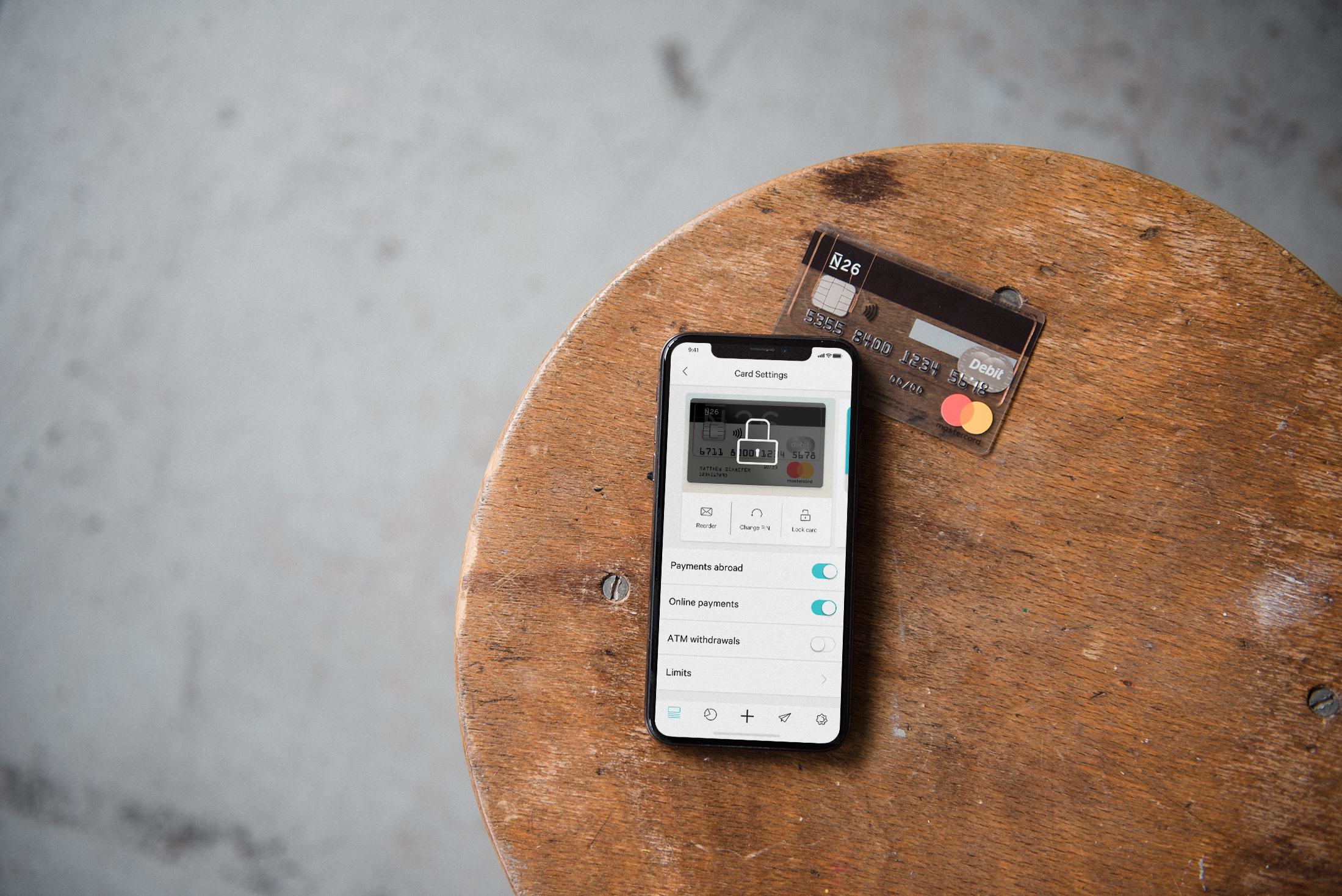 N26 Press Image with a phone showing the card settings section of the N26 app with a bank account card in the background. Both things are laying on a wooden table