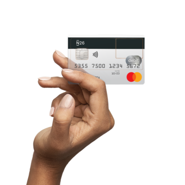 An elevated hand holding a transparent N26 credit card in their hand.