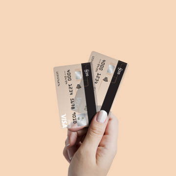 An elevated hand holding two N26 Visa cards against a beige background.
