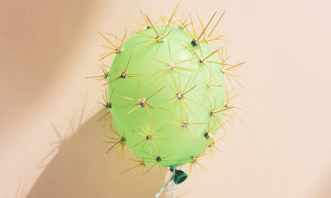 A green balloon that has cactus spikes on it.