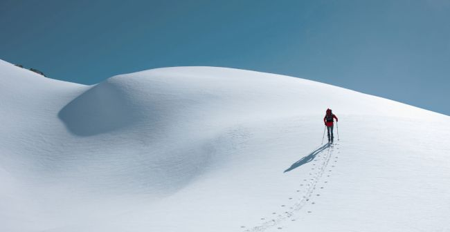 Travel Insurance Header image with a snow mountain and a guy walking on it.