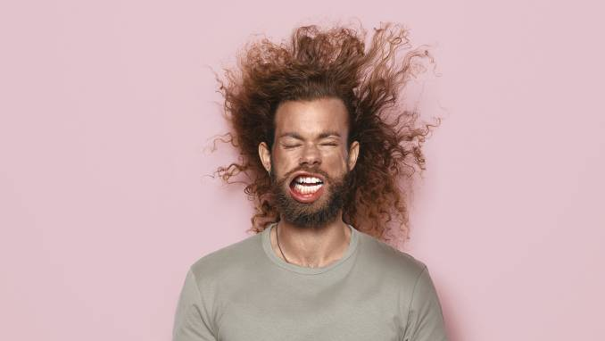 Man with beard and long hair against pink background.