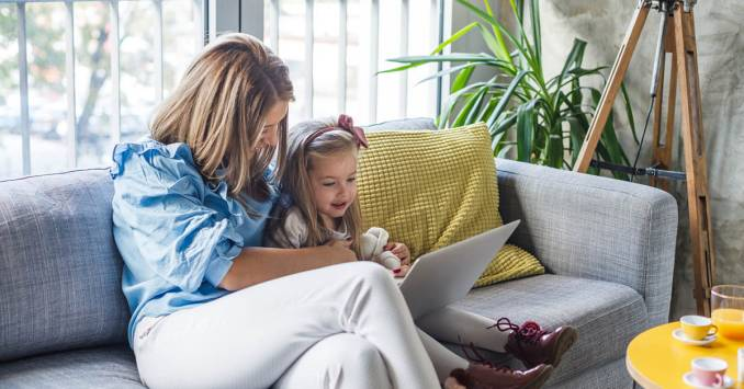 Woman with her daughter watching something on a laptop.