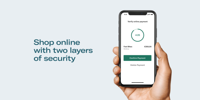 Hand holding smartphone with PSD2 payment confirmation screen displayed.