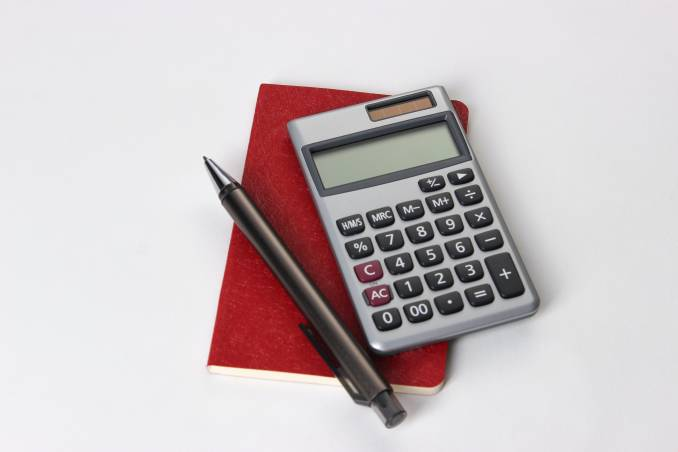 Calculator, pen and notebook on a white background.