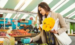 Woman holding a bouquet of yellow flowers and shopping in a local farmers' market.