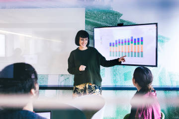 Woman explaining graph chart in a meeting.