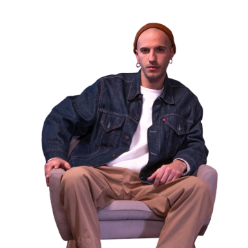 A young man wearing a beanie and sitting on an armchair.