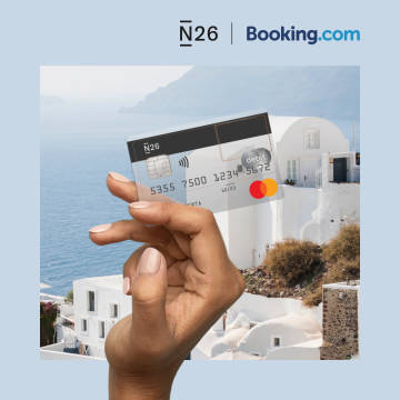 Hand holding a transparent N26 card in front of a Mediterranean vista.