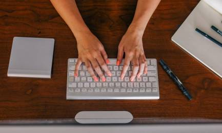 Freelance woman typing on a computer on a desk.