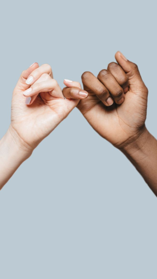 Two elevated hands against a light blue background doing a pinky swear.