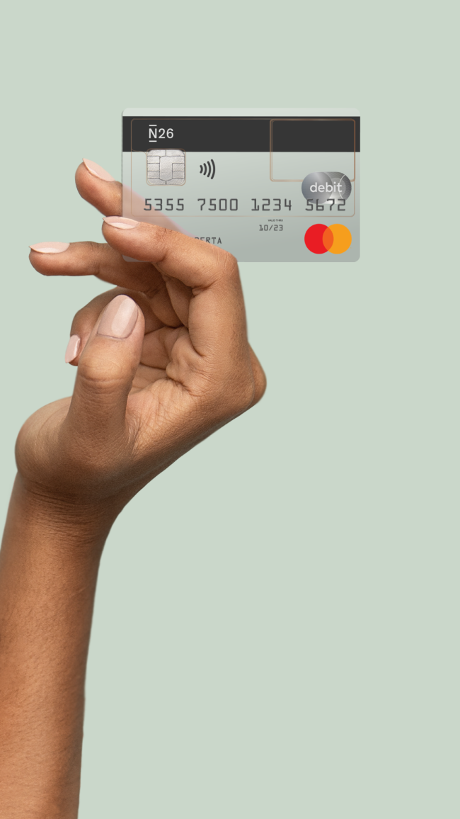 Hand holding an N26 Mastercard against a light green background.