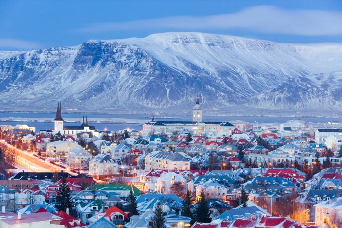 elevated view over the churches and cityscape of reykjavik with a backdrop of snow capped mountains.