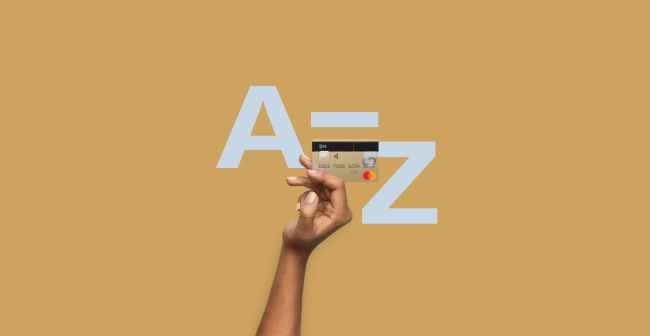 Hand holding an N26 card with the letters A and Z in the background.