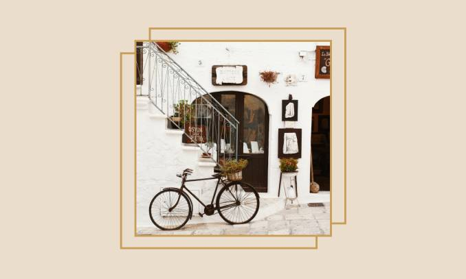 Bicycle leaning in front of a shop in an Italian village.