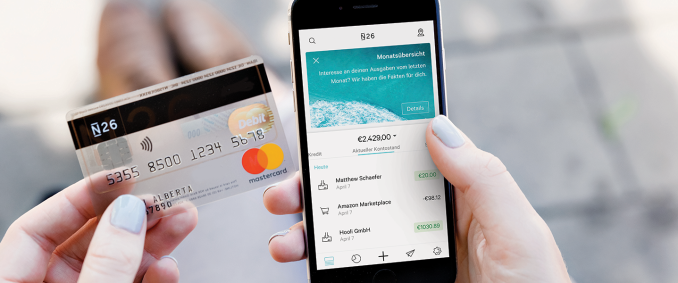 A person holding an N26 Mastercard and a smartphone with the N26 app open.