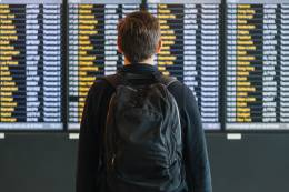 Young Man With A Backpack Checking The Flights Timetable At The Airport.