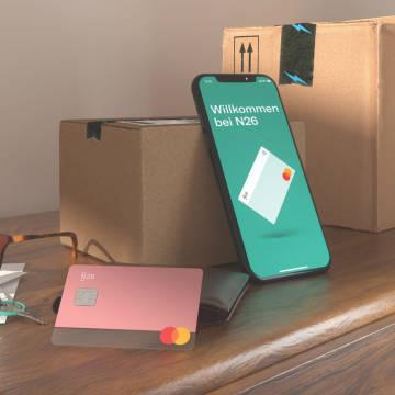 Bild einer N26 YOU Rosenkarte und einer N26 APP auf einem Tisch mit zwei Boxen.