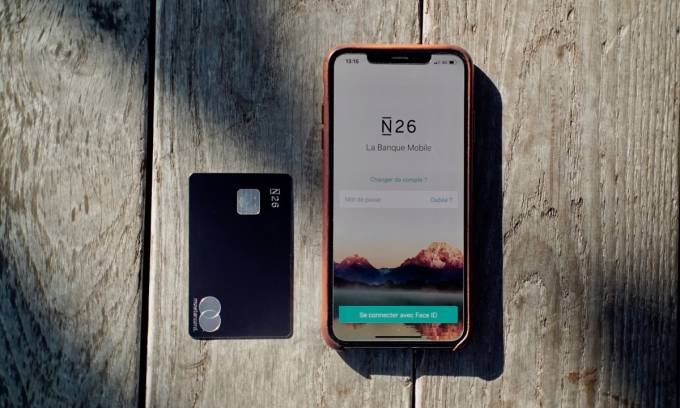 An iPhone X with the N26 app open on it and an N26 Metal card laying on a wooden surface.