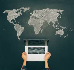 map of the world painted on a blackboard and a laptop above the paint.