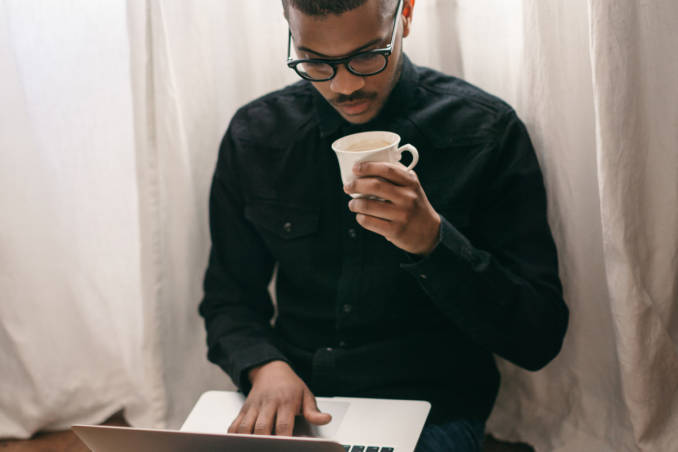 A guy using a laptop and drinking coffee.