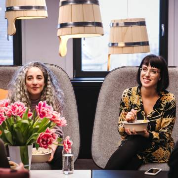 N26 Team, Two women during lunch in the office with flower in the front.