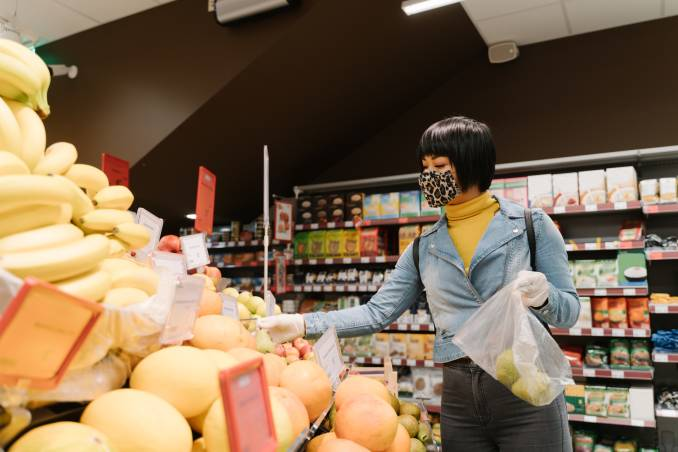 woman wearing a mask buying fruits in a supermarket.