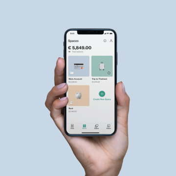 A hand holding an iPhone X in their hand with the Spaces screen open on the N26 app.