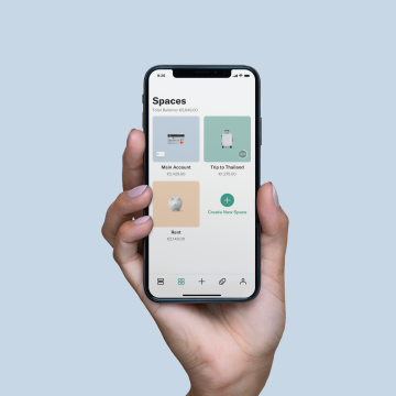 An elevated hand holding an iPhone X in their hand with the N26 App's Spaces screen open on it.