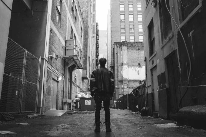 Man stands in an alley next to buildings.