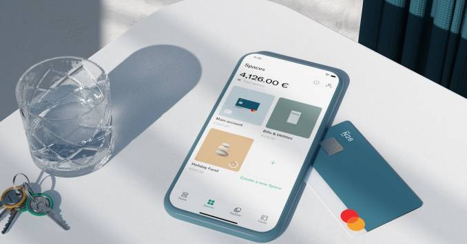 N26 Spaces on phone screen, N26 You card, keys and a glass on a table.