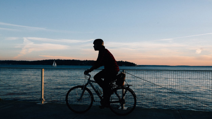 A guy riding a bike in a sunset.