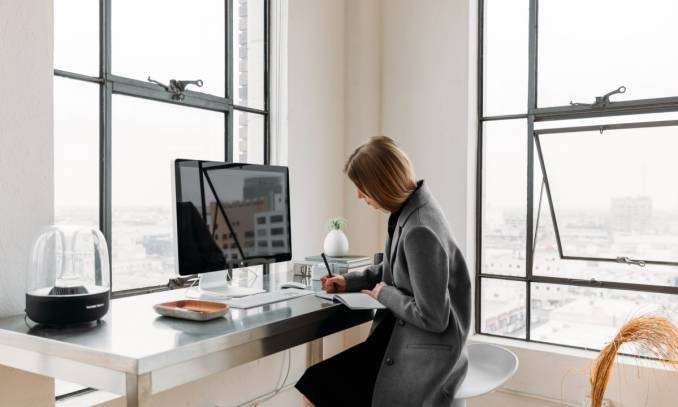 A freelancer woman working in a light apartment with a computer and notebook.