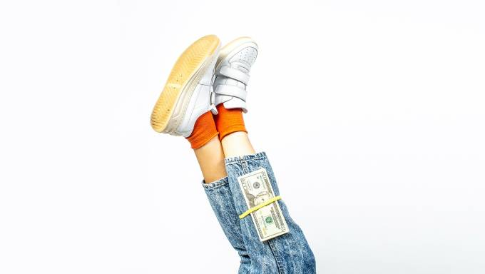 Stack of money on legs wearing jeans.