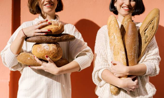 Two women holding bread.