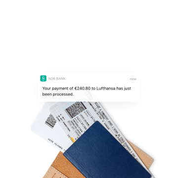 N26 You Instant Push Notification about payment to an airline with two flight tickets in the background.