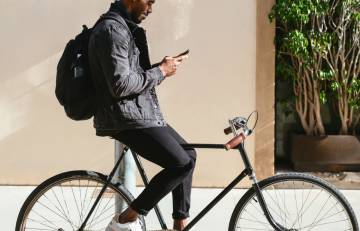 A person driving with a bike and using a smartphone.