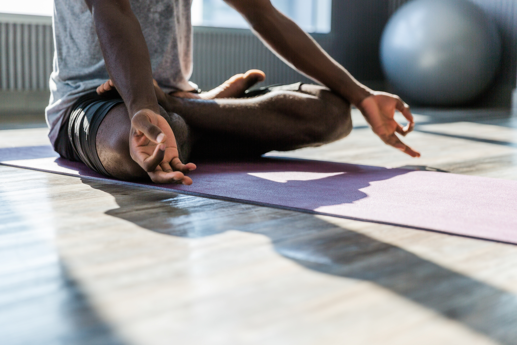Closeup of a man meditating in a bright and modern yoga studio