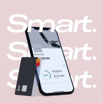 Image of a mobile phone showing a subaccount on the screen and a black debit card in the side.