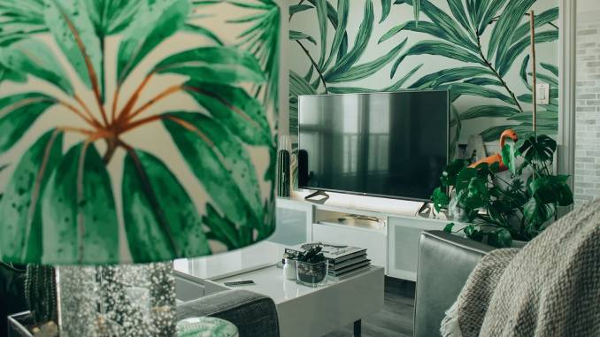 Living room with plant wallpaper and lamp.