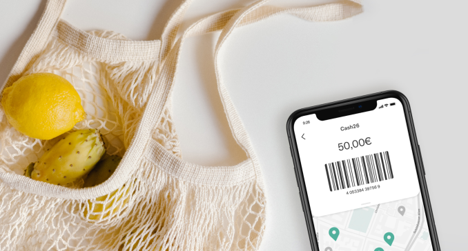 A shopping bag with some fruit next to a smartphone with the CASH26 barcode.