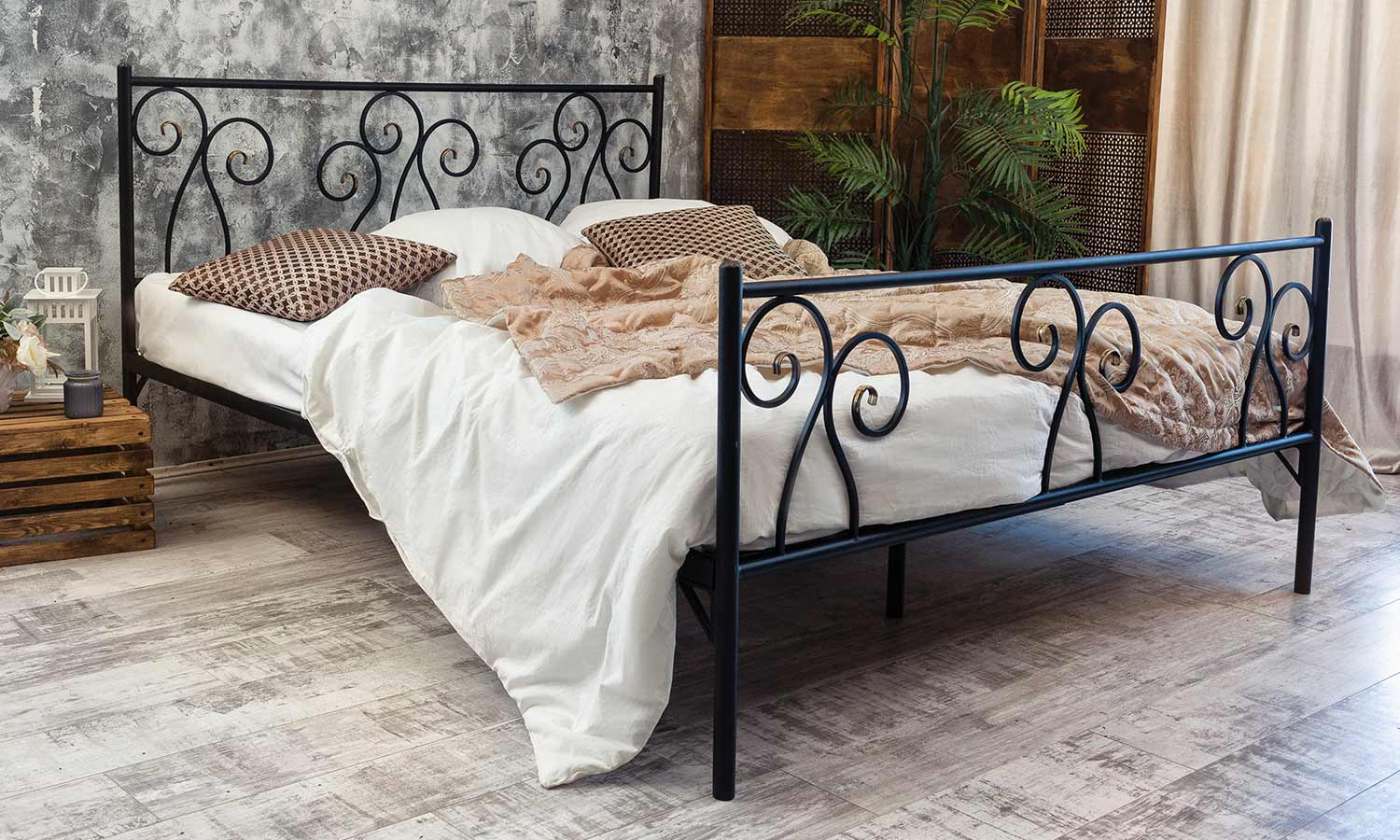 A simplistic iron bedframe with delicate swirls of metal wover int he headboard and footer.