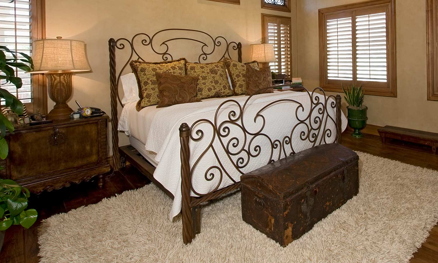 A metal bed frame with thin swirls woven throughout the headboard.
