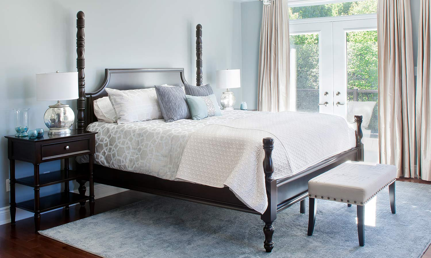A bed with two tall posts on each corner of the head of the bed, and two smaller posts for the foot-corners.