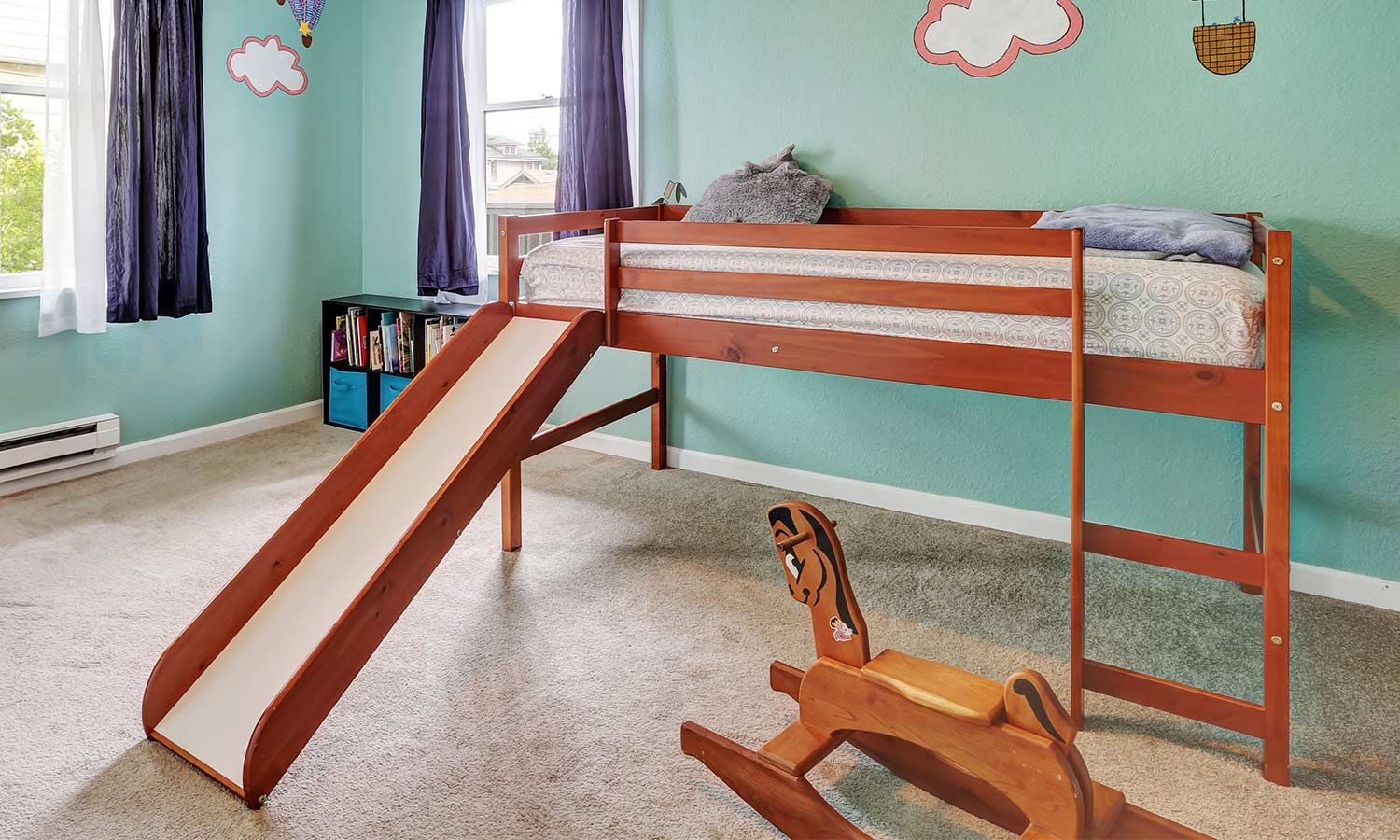 A bed lifted off the ground with a slide attached.