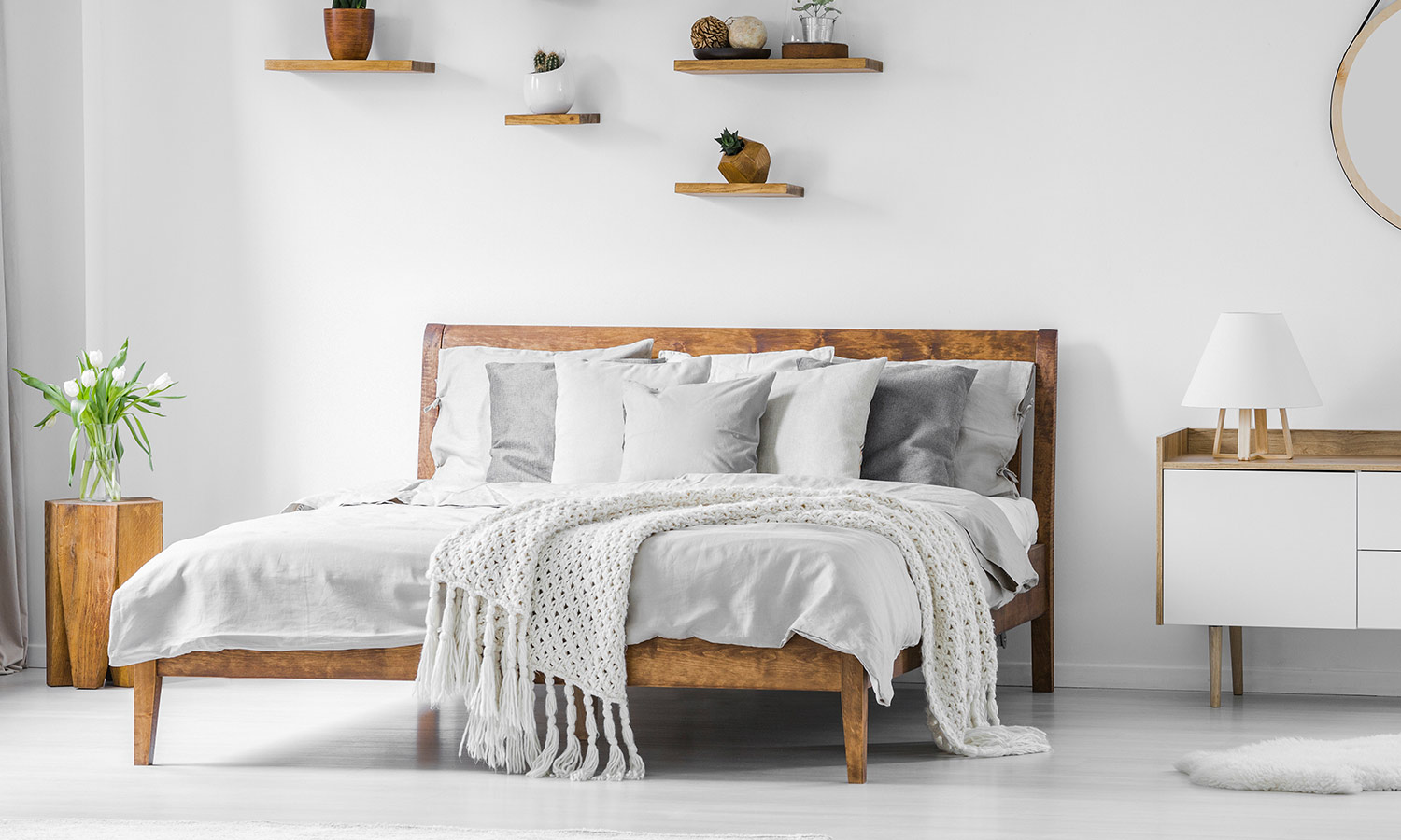 A plain wood-framed bed with modern blankets and pillows on top.